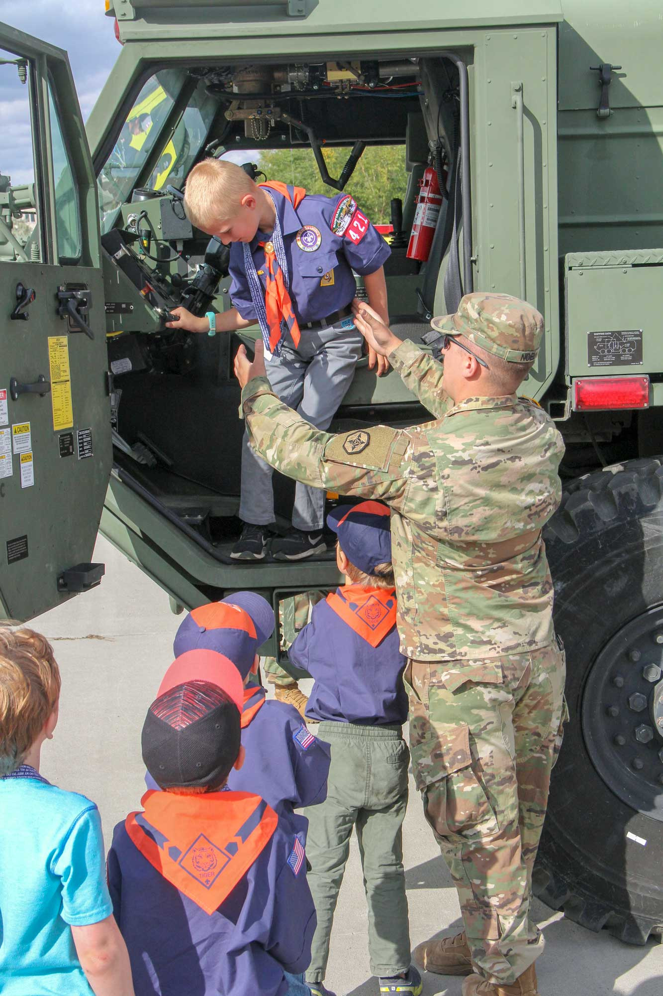 An Army Reservist helps a local Cub Scout out of a militaryvehicle during Pack 421's fall meeting last week at the Mid dleSchool. The scouts participated in a variety of activitiesand learned how emergency personnel do their jobs.