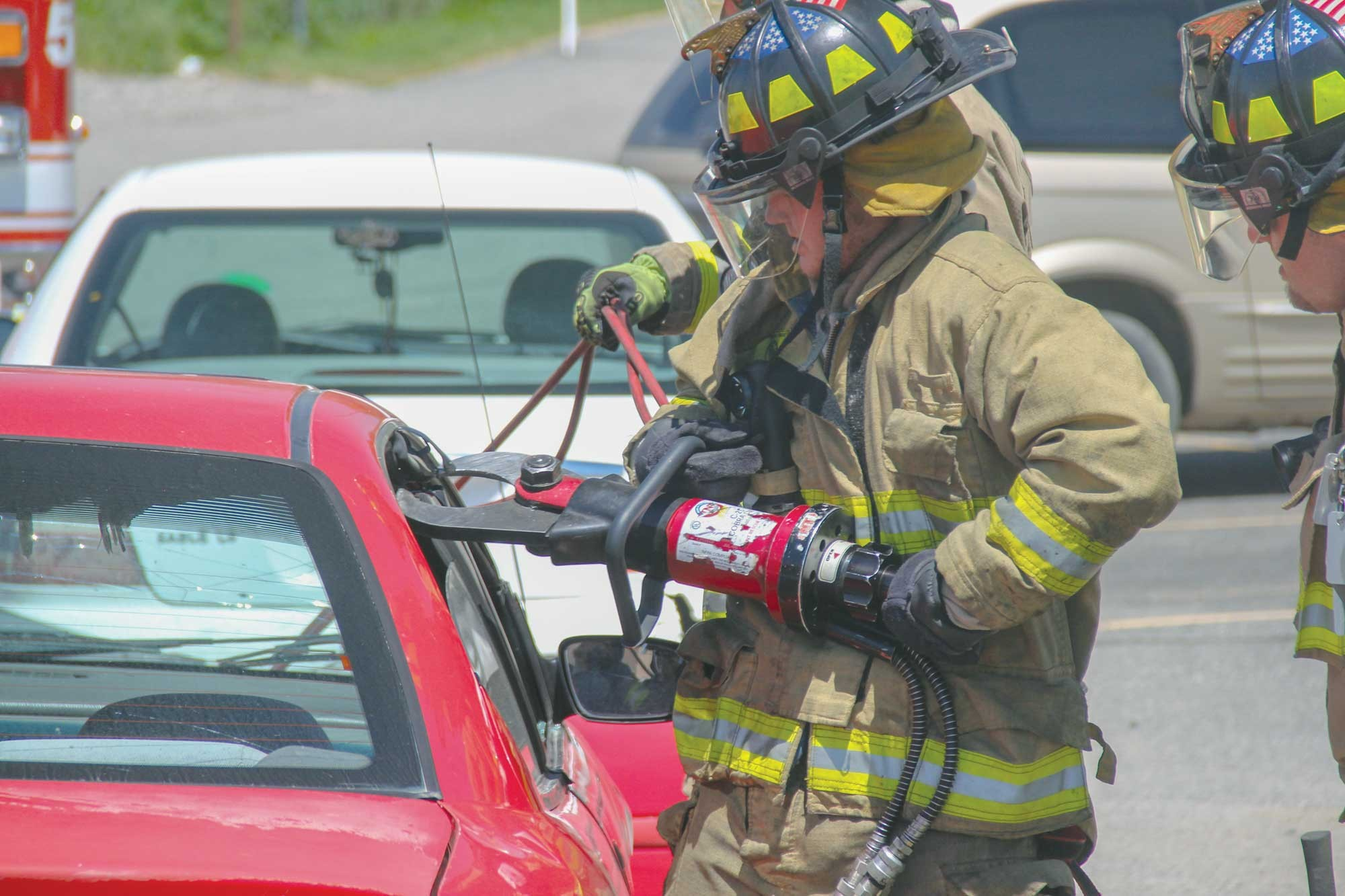 "Laurel firefighters use the ""Jaws of Life"" to cut the doors and roof off a car during an extraction demonstration at the 8th Annual Fire Safety Day in the Laurel High School parking lot on Saturday."