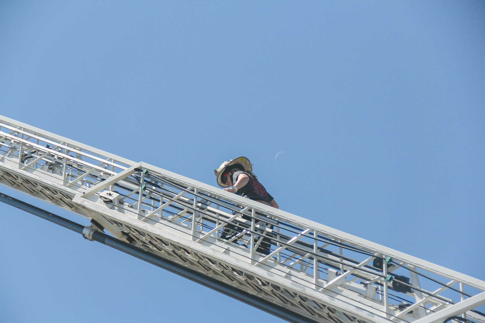A Laurel firefighter climbs a fire truck ladder during Fire Safety Day on Saturday as the waning crescent moon is seen in the background.