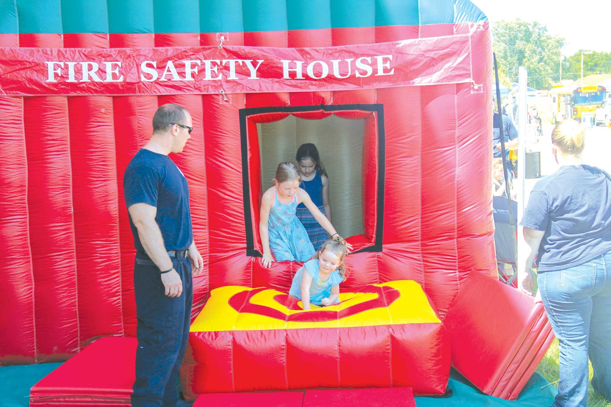 Laurel youth are seen exiting the bouncy Fire Safety House on Saturday.