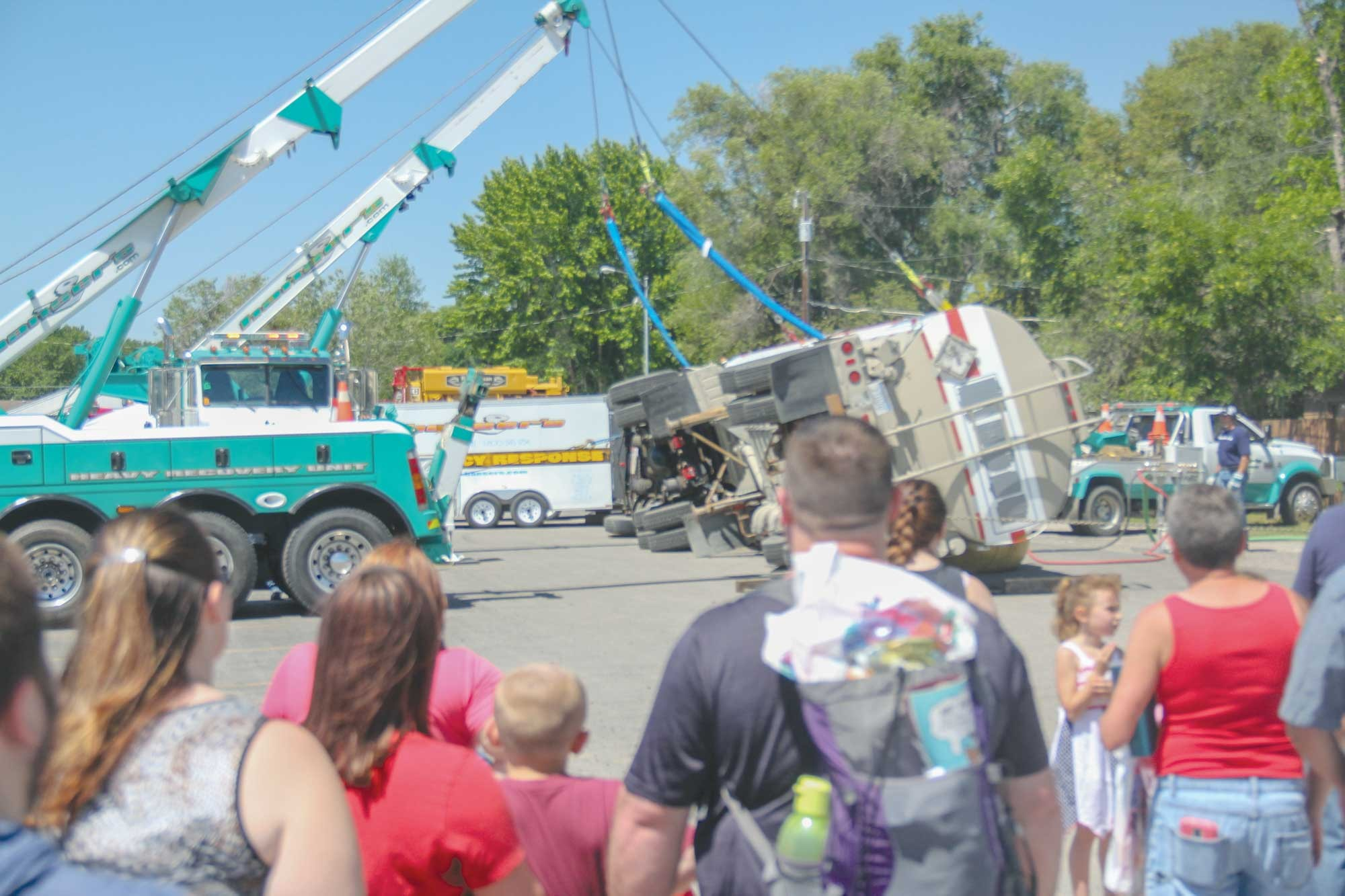 Area kids and parents watch as Hansers' employees demonstrate how they lift an overturned semi on Fire Safety Day at the LHS parking lot.
