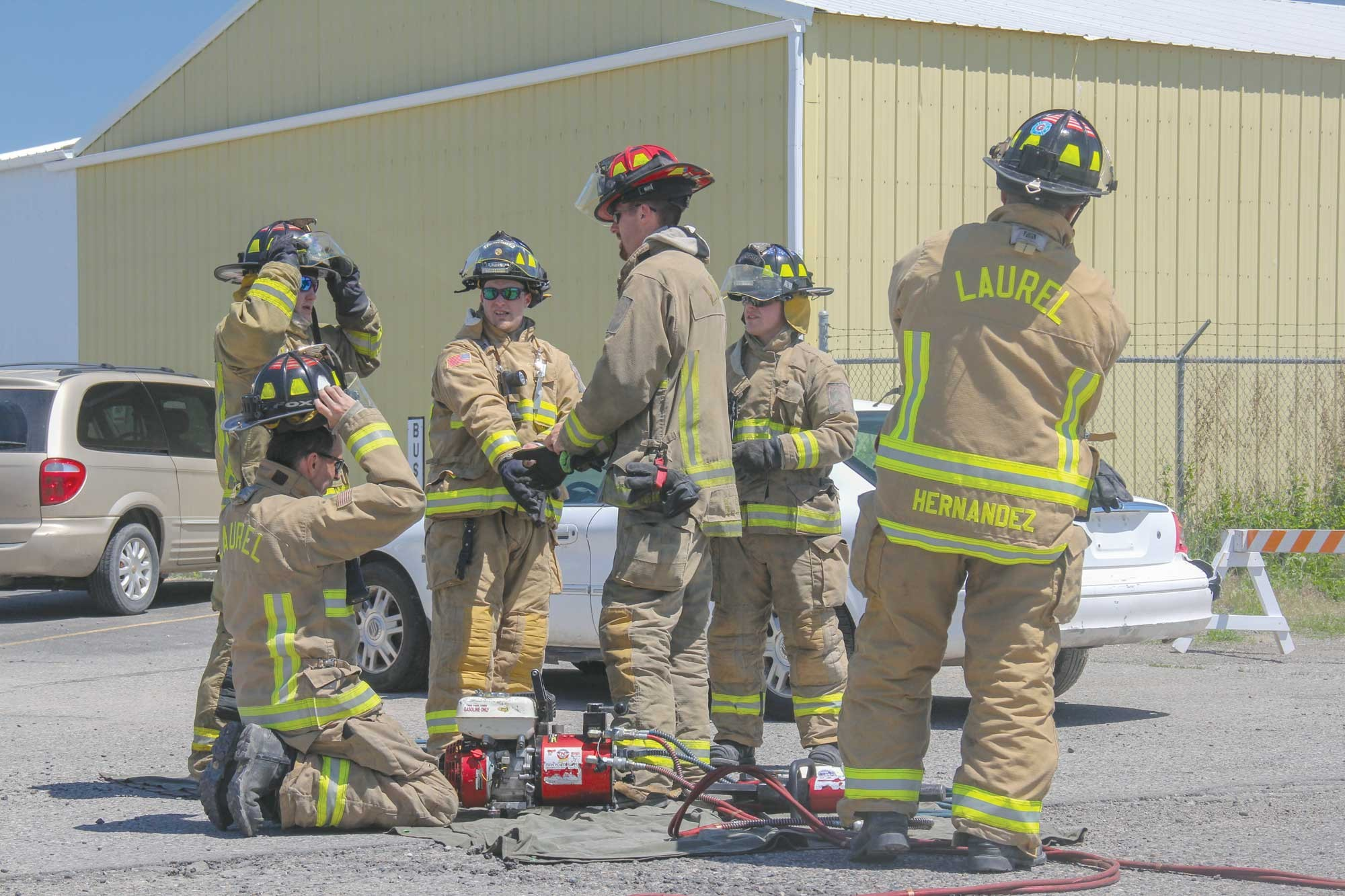 Members of the Laurel Volunteer Fire Department finish putting on their gear before they give a car extraction demonstration.